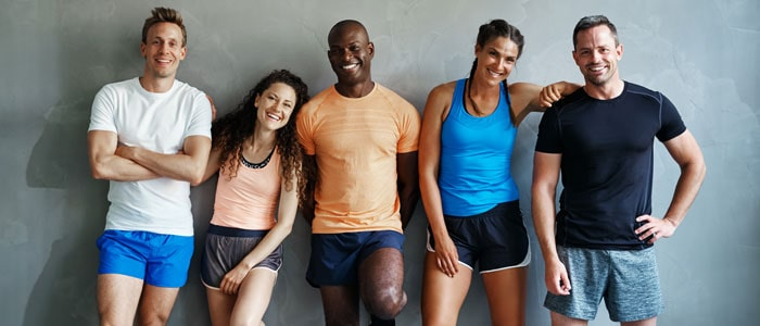 group of five people in exercise clothing posing