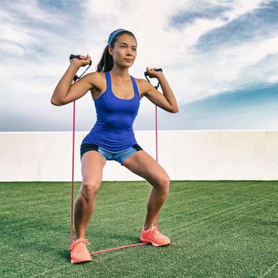 woman doing Resistance Band Squat variations