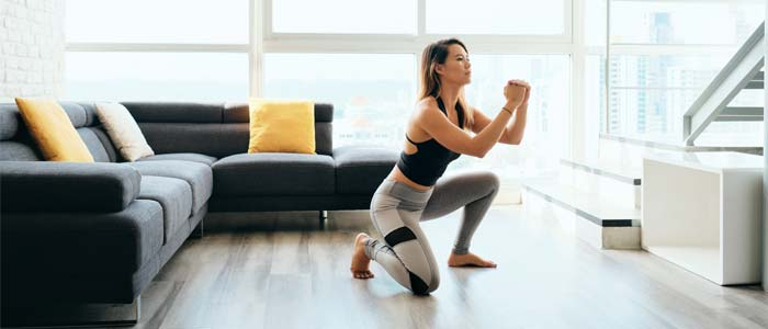 woman doing Surrender Squat variation from home