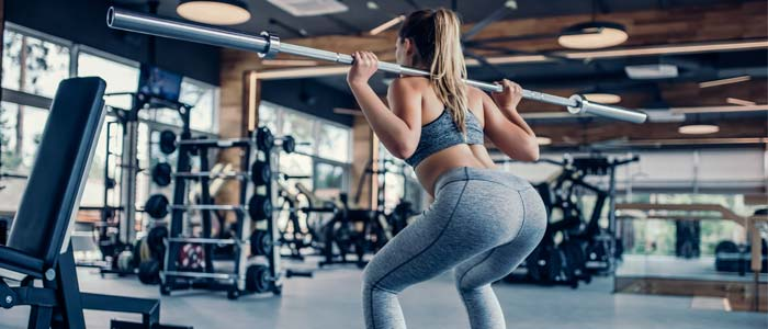 woman doing a back Squat with a barbell and weights