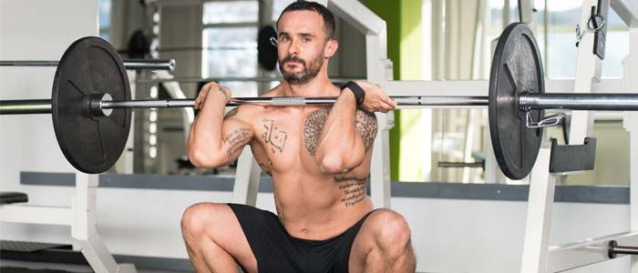 man doing a Front Squat with a barbell and weights