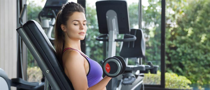 woman in the gym doing Incline Dumbbell Curl on a weight bench