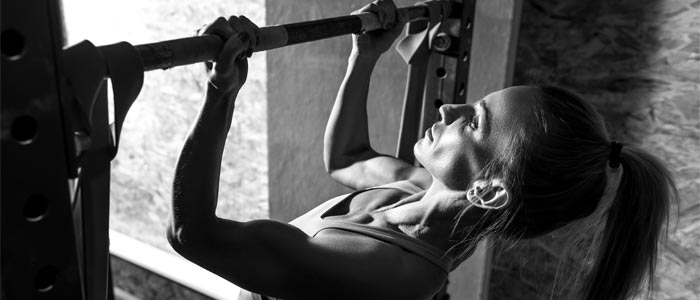 woman doing chin ups to improve bicep strength