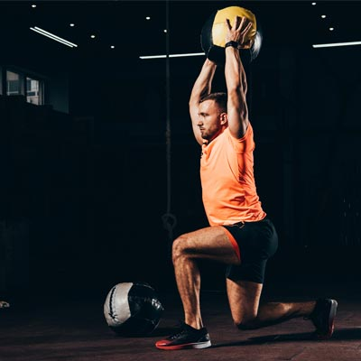 man doing overhead lunges with an exercise ball