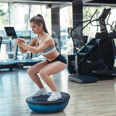 Woman doing squats on a Bosu® ball