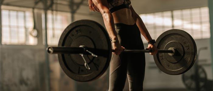 woman doing a deficit deadlift to strengthen her core