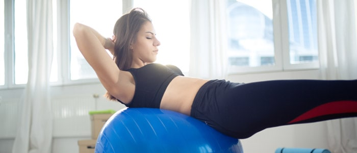 A woman doing crunches on an exercise ball in her home