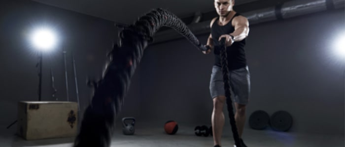 Man in a garage gym training with battle ropes
