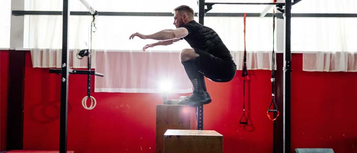 man doing box jumps in a gymnasium