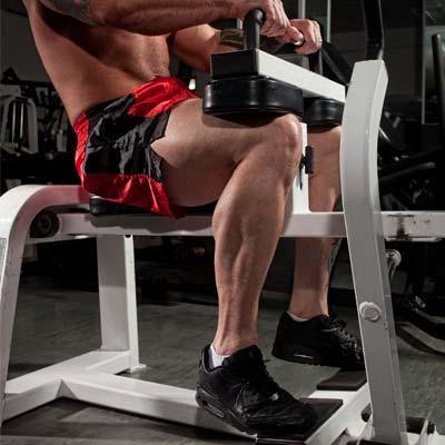 man using a weight machine to do calf raises