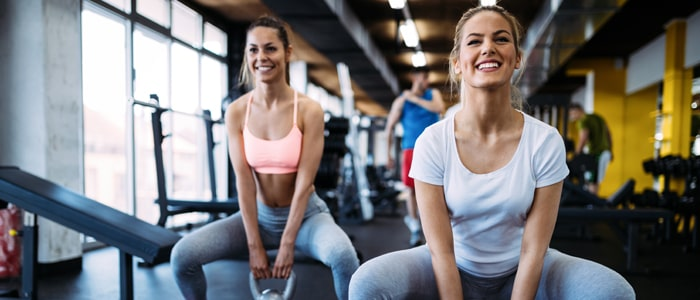women squatting with kettlebells at the gym