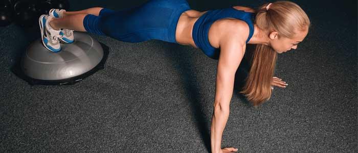 woman doing a renegade row on a Bosu® ball