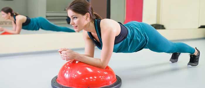 woman doing a plank on a Bosu® ball