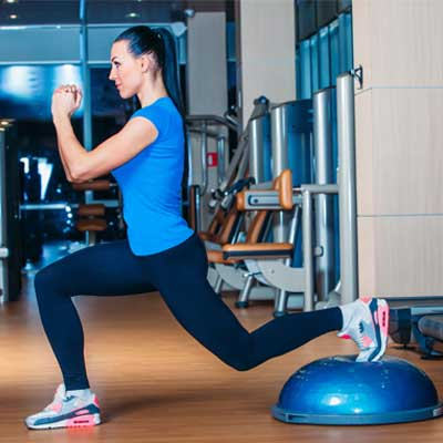 woman doing lunges on a Bosu® ball
