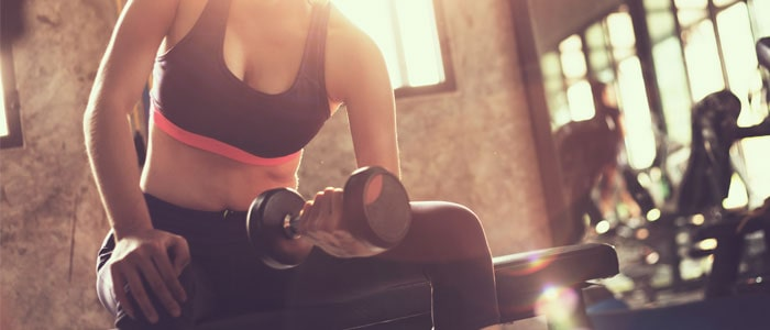 woman in the gym doing bicep curls with a dumbbell