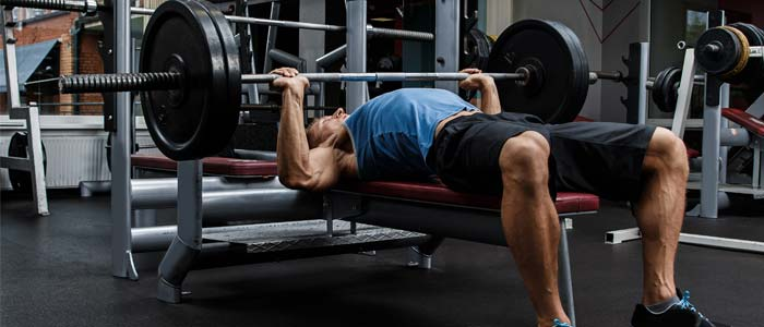 man lifting weights on a weight bench at the gym and building muscle