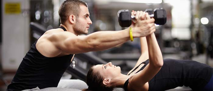 Woman laid on a bench lifting dumbbells with the aid of a trainer, building muscle