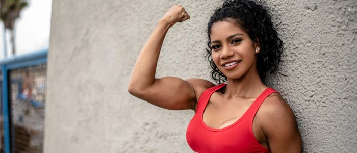 woman leaning against a wall showing her muscles