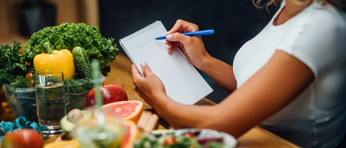 woman sat at a table with ingredients planning her meals