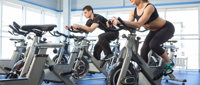 people training on exercise bikes at the gym