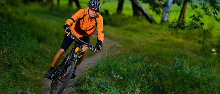 Man cycling down a hill in a wooded area