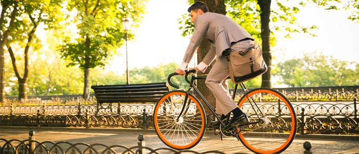 Man cycling through a city area to work