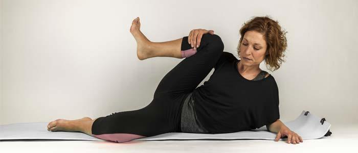 Woman on a yoga mat doing leg stretches