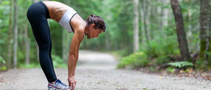woman outside in nature stretching down to touch her toes