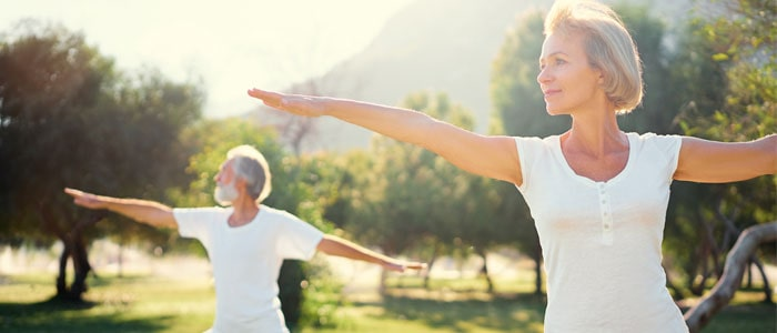 two older people doing yoga outside