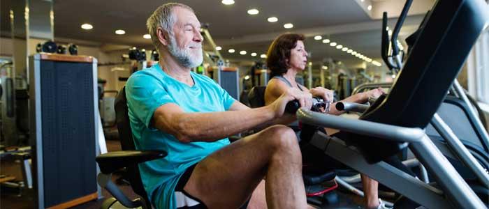 elderly people on recumbent bikes at the gym
