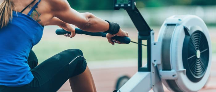 Woman training on an air resistance rowing machine