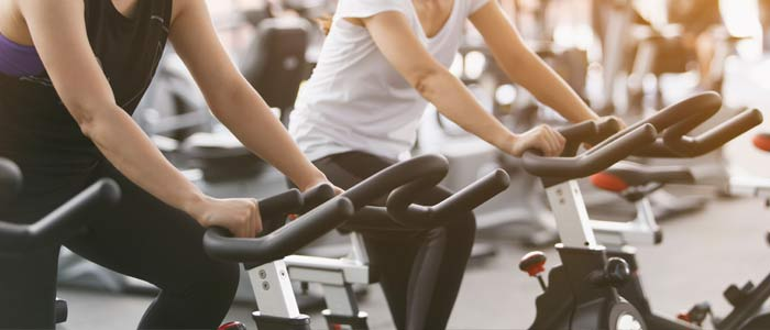 people on exercise bikes at the gym