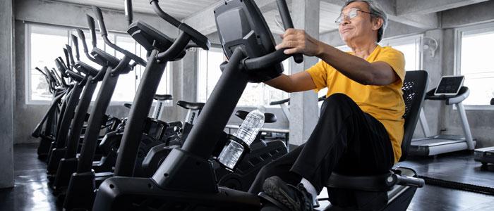 An elderly man exercising on a recumbent exercise bike