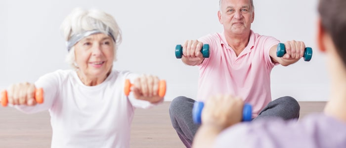 two elderly people lifting light weight dumbbells