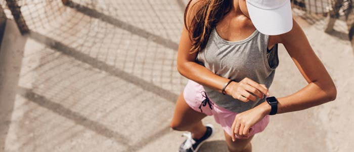 woman outdoors checking her smart watch before her endurance training workout