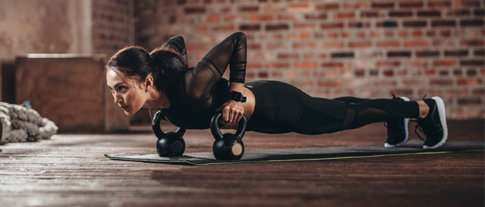 woman doing kettlebell exercises on a fitness mat in the gym