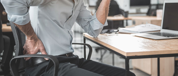 man sat at his desk holding his back as if in pain