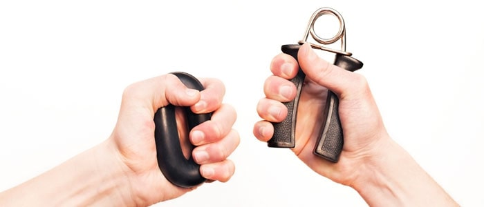 two hands using grip strengtheners to build hand muscles