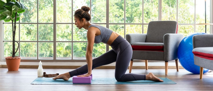 Woman doing yoga at home on a yoga mat with a yoga block