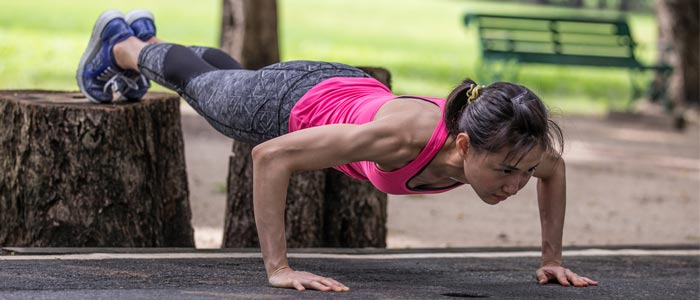 a person performing a decline push up outside