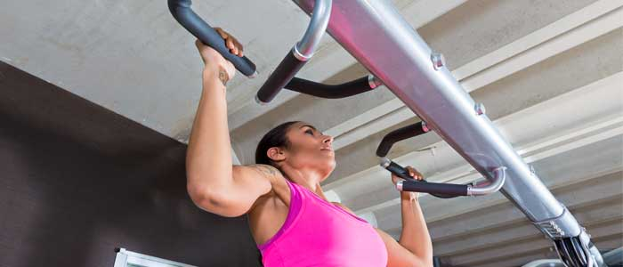 woman using a gym machine to do pull ups