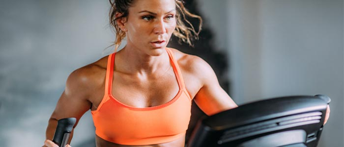 woman sweating using a cross trainer