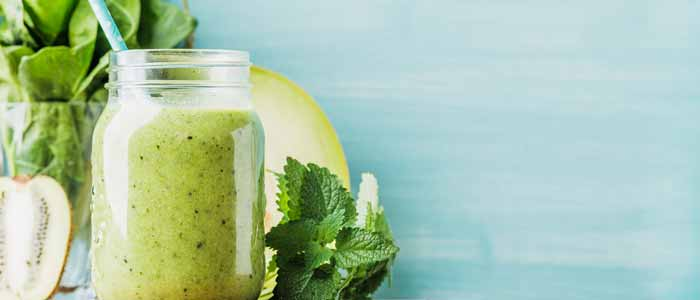 Blue background with a green smoothie surrounded by green foods that it is made from: kiwi, mint etc as a healthy snack