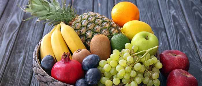 healthy snacks fruit bowl made up of apples, grapes, pinapple, bananas, kiwis, oranges, lemons, limes and a pomegranate