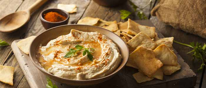 a bowl of hummus with a side of tortilla chips as a healthy snack