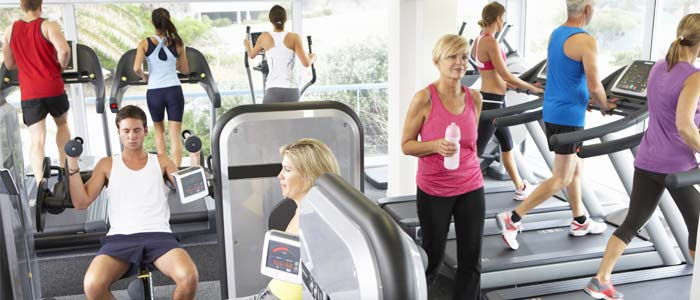 A busy gym, showing people on treadmills, lifting weights and just wandering around