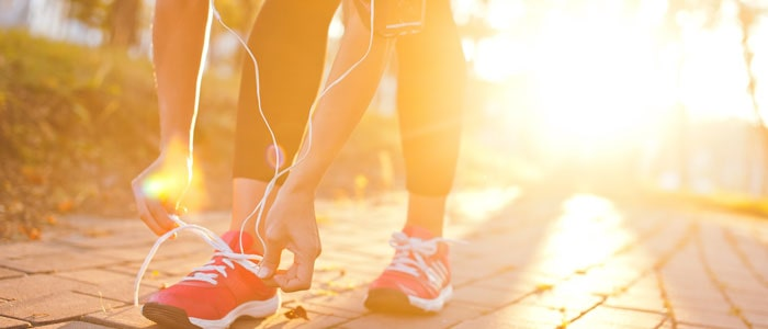 woman tying her shoelaces outside in the morning - fitness questions