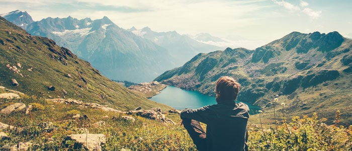 man sat on the ground looking out over the mountains and lakes