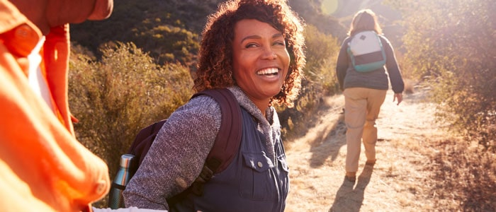 woman smiling at someone whilst outside hiking