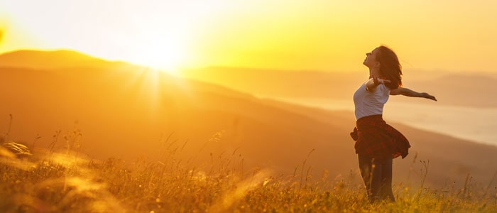 woman outside, arms wide, embracing the sunlight, a benefits of being outdoors
